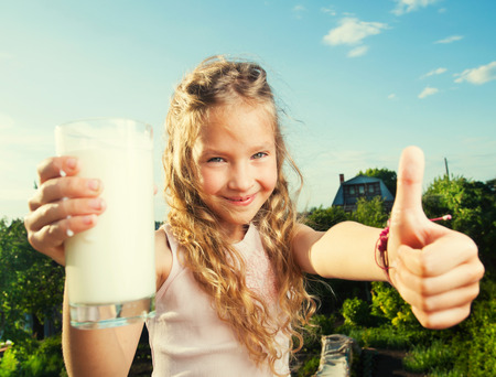 human milk: Girl holding glass with milk. Happy child at summer
