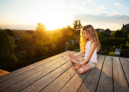 Girl meditating outdoors. Child practicing yoga
