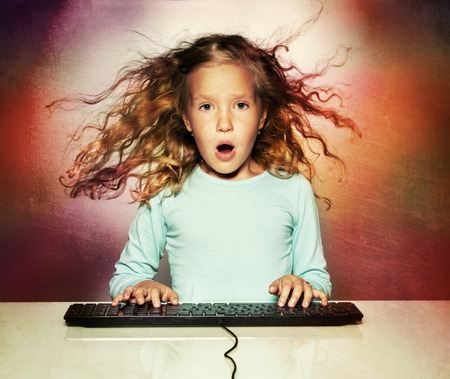 surprised child: Surprised little girl with computer keyboard. Child looking at computer Stock Photo