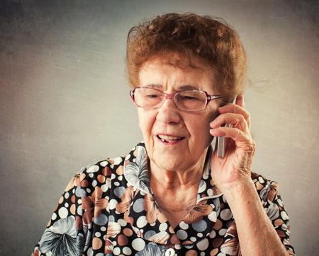 노인 휴대 전화를 이야기합니다. 늙은 성인의 성숙한 여인