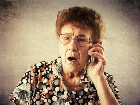 Surprised seniors talking mobile phone. Old adult mature woman. Shock photo