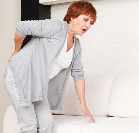 espada: Mujer adulta que tiene un dolor de espalda. Madura mujer tiene dolor en la espalda Foto de archivo