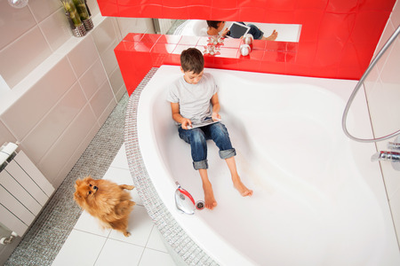 10 12: Boy hiding in the bathroom, playing in tablet. Computer Addiction, gambling, lie
