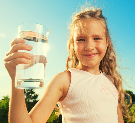Girl holding glass with water. Happy child at summer Banque d'images