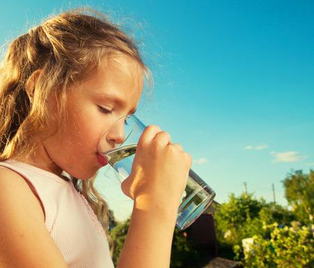 tomando agua: Ni�a de la celebraci�n de vidrio con agua. Ni�o feliz en el verano