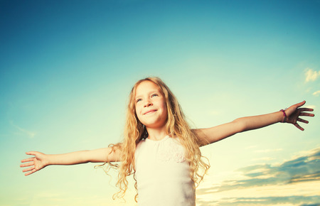 outstretched: Child with arms outstretched. Freedom. Girl on a background of the sky