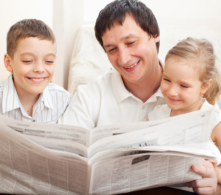 35 40: Happy family reading a newspaper. Father with daughter and son Stock Photo