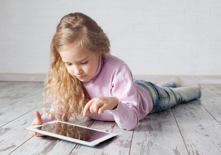 Child with tablet lying on floor. Girl playing laptop computer Фото со стока