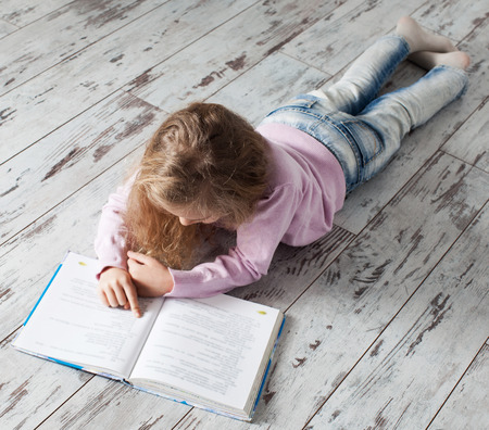 ni�os leyendo: Ni�o que lee el libro en casa. Chica haciendo la tarea