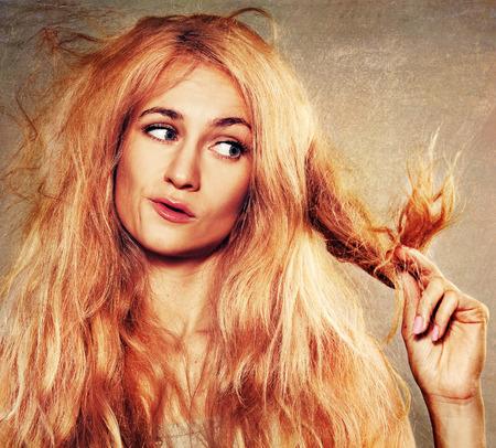 Junge Frau schaut auf Spliss. Beschädigte lange Haare