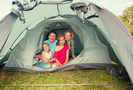 3 5 years: Family with children in a tent. Camping. Happy parents with kids at summer vacations