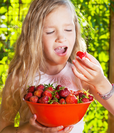 6 7 years: Child with strawberry. Girl with fruit, berry at garden Stock Photo