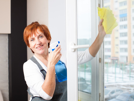 Mature woman cleaning window. Female washing window