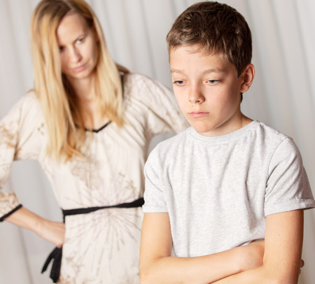 family problems: Mom swears by son. Conflict, problems in family. Sad mother and child Stock Photo