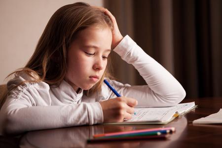 niños escribiendo: Niño haciendo la tarea. Escrito muchacha triste, reeding