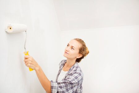 Woman doing repairs. Female paints the wallpaper roll photo