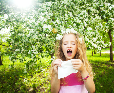 Sneezing girl. Child with a handkerchief. Allergy