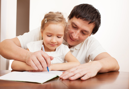 father teaching daughter: Father helping daughter doing homework. Parent with child writing Stock Photo