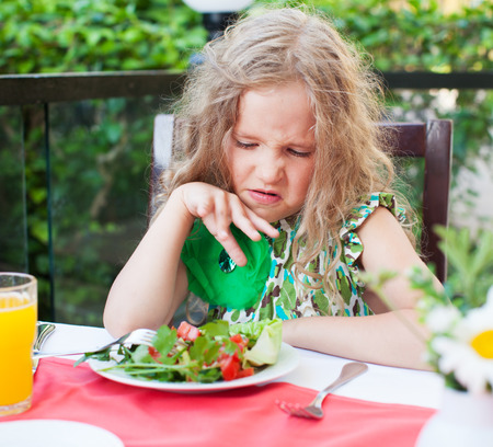 Girl does not like the food. Child with disgust looking at vegetable salad