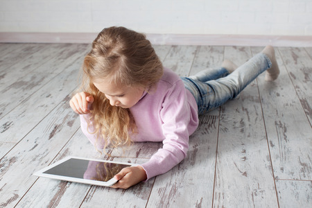 heated: Child with tablet lying on floor. Girl playing laptop computer Stock Photo
