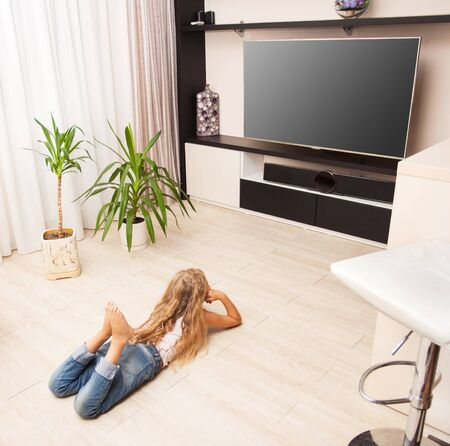 heated: Child laying on the floor and watching TV at home