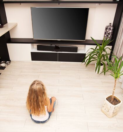 heated: Child watching TV at home. Girl looking at television Stock Photo