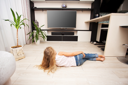 laying little: Child watching TV at home. Girl looking at television Stock Photo