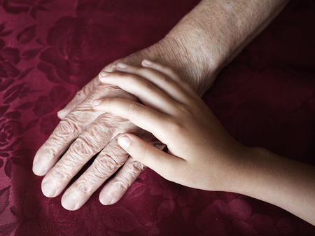 80 plus adult: Two hands. Old and young. Childs hand on arm of an mature woman Stock Photo