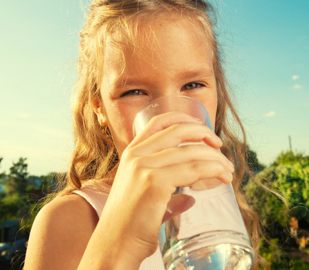 Girl holding glass with water. Happy child at summer Standard-Bild