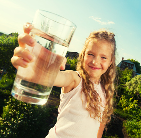 Girl holding glass with water. Happy child at summer Foto de archivo