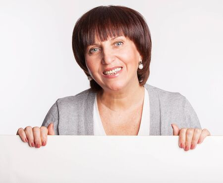 1 woman only: Mature woman holds a placard. Female showing blank with advertisement Stock Photo