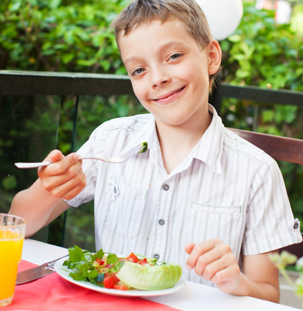 hungry kid: Boy eating salad at a cafe. Teenagerl eating outdoors Stock Photo