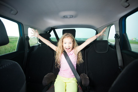 handcarves: Child in car. Happy girl wearing seatbelts
