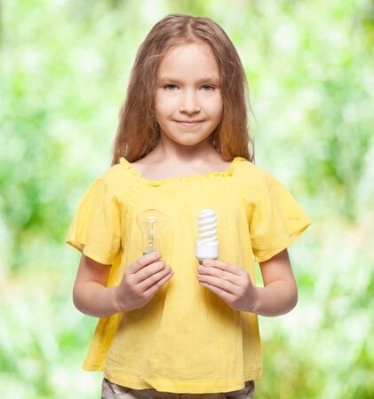 incandescent: Child with bulbs. Girl holding an energy-saving and incandescent lamp