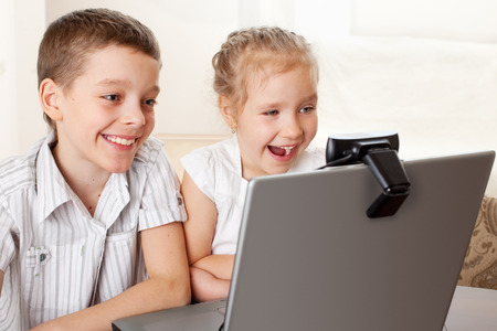 skype: Ñhildren communicate with online. Happy kids with laptop at home Stock Photo