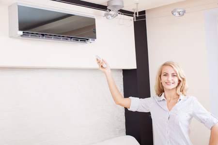 Female holding a remote control air conditioner at home. Happy young woman on sofa