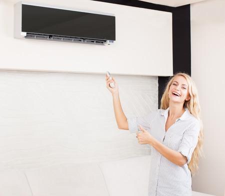 航空ショー: リモート コントロール、エアコンを家庭で保持している女性。ソファーで幸せな若い女