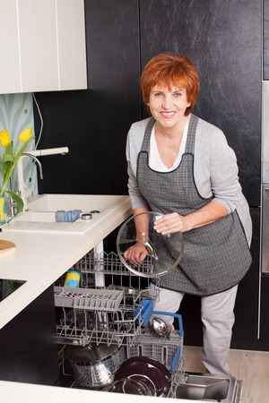 stereotypical: Woman folding the dishes in the dishwasher. Female at kitchen. Housework