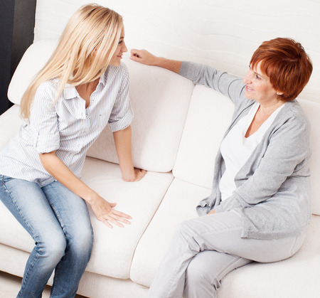 blonde mom: Mother with daughter at home. Happy women sitting at sofa. Family Stock Photo