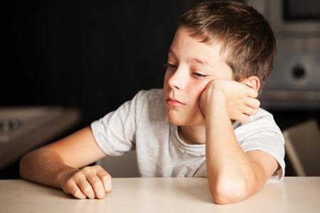Muchacho triste en casa. Niño infeliz. Las emociones hacen hincapié en la adolescencia