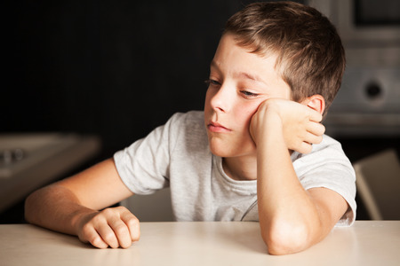 Sad boy at home. Unhappy child. Emotions stress at teenager Standard-Bild