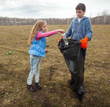 scavenge: Children cleaning scavenge. Children collect garbage bag in the woods