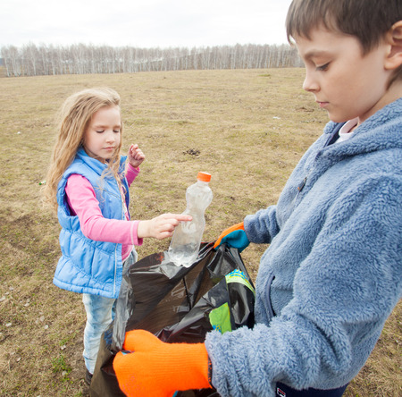 Children cleaning scavenge. Children collect garbage bag in the woods