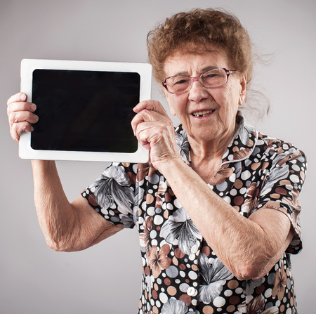 visual screen: Old woman holding a tablet in the hands of. Seniors with tablen pc Stock Photo