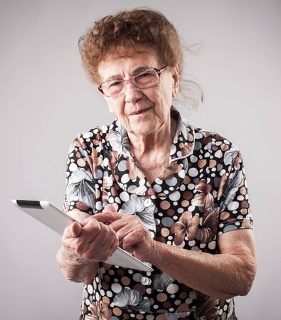 80 plus years: Old woman holding a tablet in the hands of. Seniors with tablen pc Stock Photo