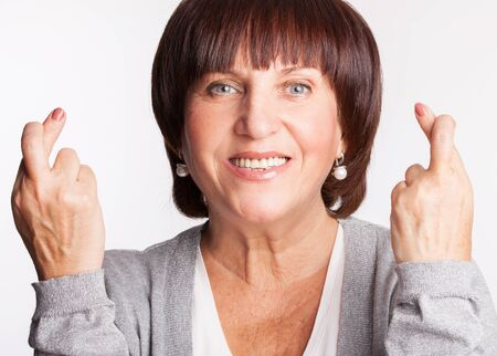 crossed fingers: Mature woman with crossed fingers. Female showing a gesture with hands. Luck, wish