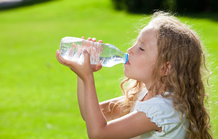 green water: Child drinking water. Girl outdoors Stock Photo