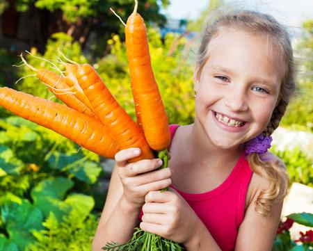 niños comiendo: Niño con zanahoria. Muchacha con los vehículos en el jardín