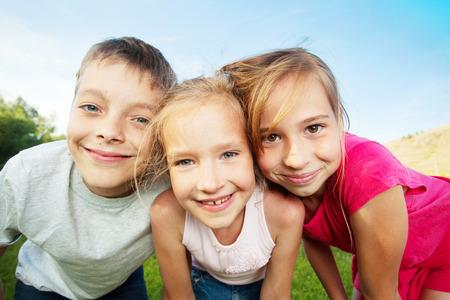 caras felices: Niños felices al aire libre. Amigos en verano