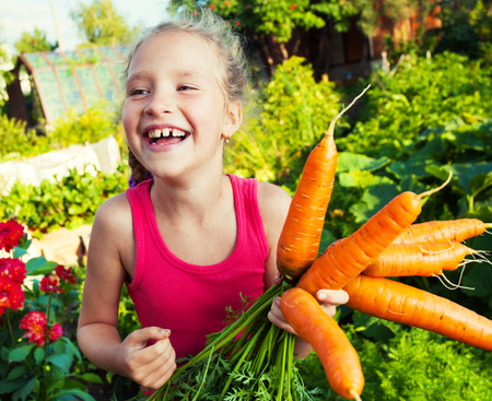 marchew: Child with carrot. Girl with vegetables in garden